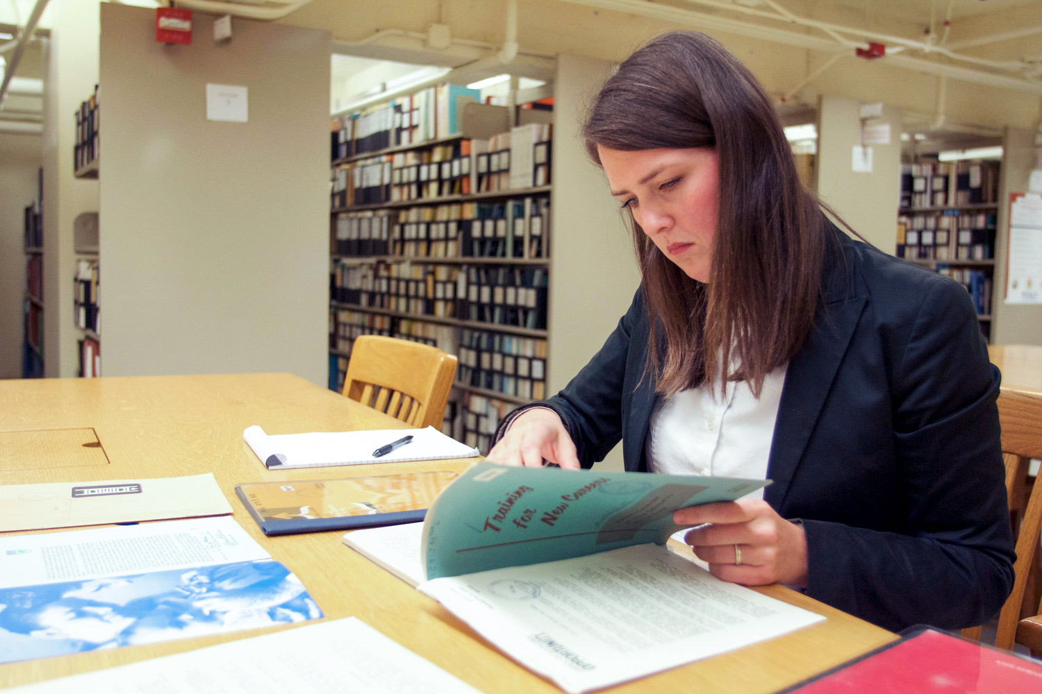 Claire Dunning in the library examining old government training manual