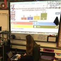 Photo of teacher sharing data on screen in classroom
