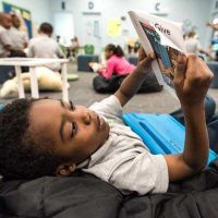 Photo of young student laying on bean bag reading paper book with device on lap