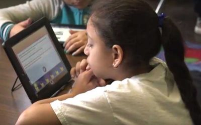 Photo closeup of student reading on her tablet device