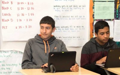 Photo of two students seated with laptops in front