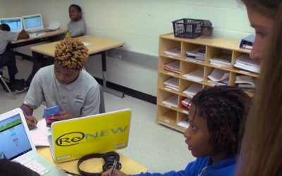Photo of teacher in classroom where students are working in small groups and on devices