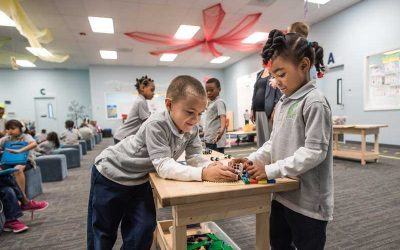 Photo of two students working collaboratively on Legos at table