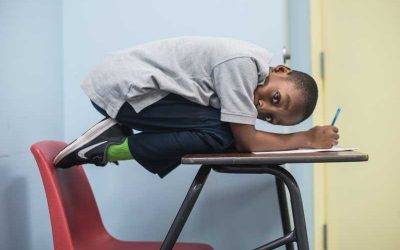 Photo of student crouched ontop of desk