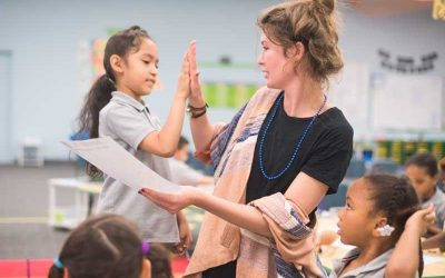 Photo of student and teacher giving each other high-five celebrating sucess