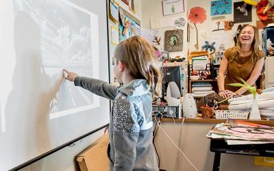 Female student points at white board while teacher looks on, smiling