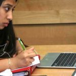 Photo of student working on her laptop and writing by hand