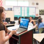 Photo closeup of teacher with open laptop speaking to students in classroom