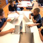 Overhead shot of five students sitting at desk, working off of laptops