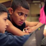 Photo of two students working together on laptops and in conversation
