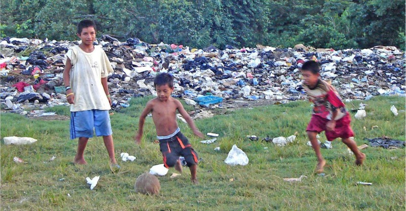 Children playing in trash-ridden field