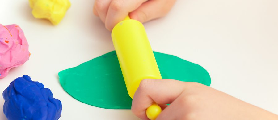 A photo of a child with play dough is used as a sensory toy for children with autism.