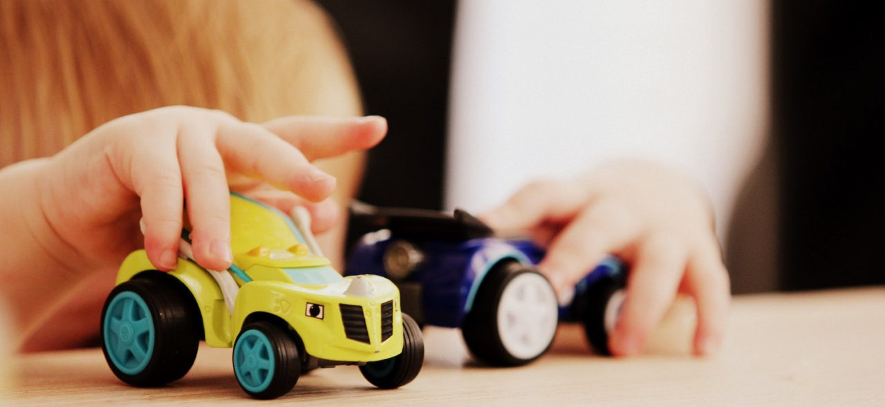 A kid playing with toy trucks.