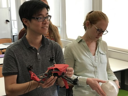 Students examine a 3D printed drone and a round component designed to hold a stylized table's legs in place.