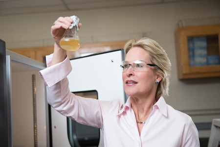 Frances Arnold looks into a chemical flask.