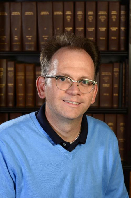 Brian Stoltz in front of a bookshelf.