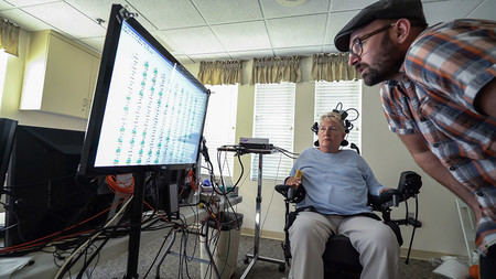 A man and a woman in a wheelchair examine a screen