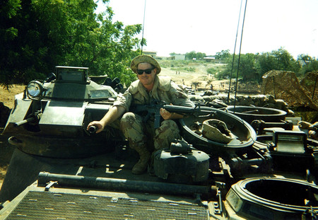 Shane Eagan, an electrician from Caltech's electrical shop, rides atop a vehicle in Mogadishu, Somalia, circa 1993.