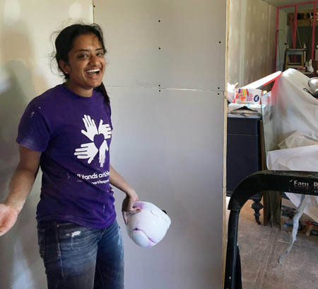 In Texas, junior Meera Krishnamoorthy installs drywall in partnership with All Hands All Hearts, an organization that rebuilds homes after natural disasters.