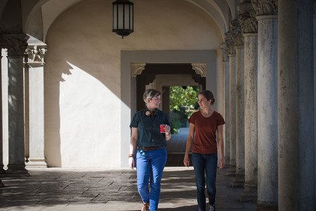 Fourth-year graduate student Giuliana Viglione (left) and her mentee, first-year Cora Went (right) walk through a hallway.
