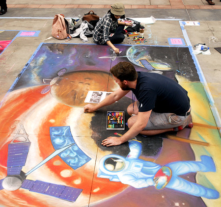 Keane (bottom) and Li apply the finishing touches to a planetary science/space exploration-themed chalk drawing at the festival on June 16.