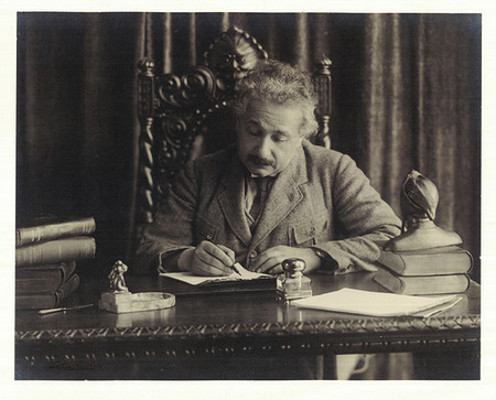 Einstein writes by hand at his desk. A bust of Dante sits on the corner of the desk near some books.