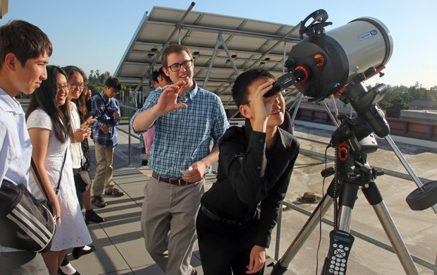 Garreth Ruane, a postdoctoral scholar in astronomy, shows visiting students from South Pasadena High School filtered views of the sun.