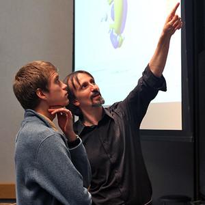 Teachers points to chalkboard