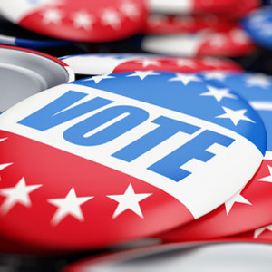 """An image of red, white, and blue buttons reading """"vote."""""""