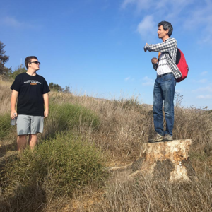 Paul Asimow, the Eleanor and John R. McMillan Professor of Geology and Geochemistry, talks to students from atop a stump during the Frosh Camp geology hike.