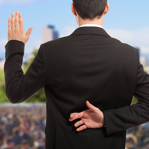A politician stands on a stage in front of a large crowd taking an oath of office. His fingers are crossed behind his back
