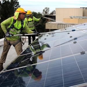 Photo of men cleaning solar panels.