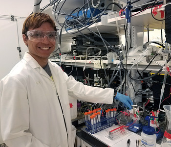A photo of Gianmarco Terrones in front of a chemistry bench crowded with test tubes and vials.