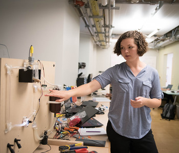 Caroline Paules gestures towards valves and tubing used in her research