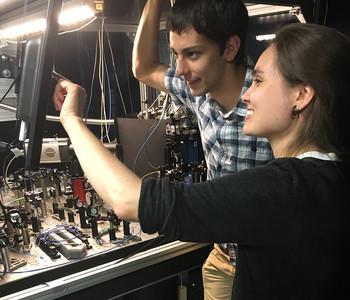 Physics student Noah Huffman with an experiment apparatus