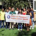 members of the Caltech Postdoc Association hold a banner for Postdoc Appreciation Week.