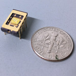 A small integrated circuit rests on a surface next to a time, which is comparable in size