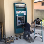 A workman helps finish the installation of an ATM on the west side of Chandler.