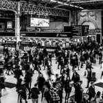 A black-and-white photograph of a crowd of people moving through a train station.
