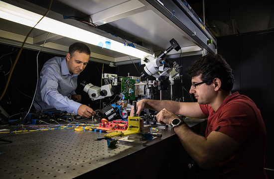 photo of Ali Hajimiri and Behrooz Abiri working with the camera sensor setup in their lab