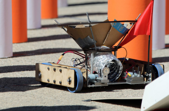 A Team Fridge robot at the end of the pylon section awaits the handoff of a ball for delivery to the end of the course.