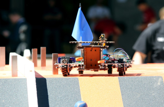 The Team V15ta robot drops a ball down the ramp at the end of the obstacle course.
