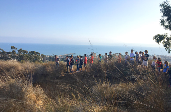 Students gather atop a bluff overlooking the ocean during a geology hike that is part of Frosh Camp.