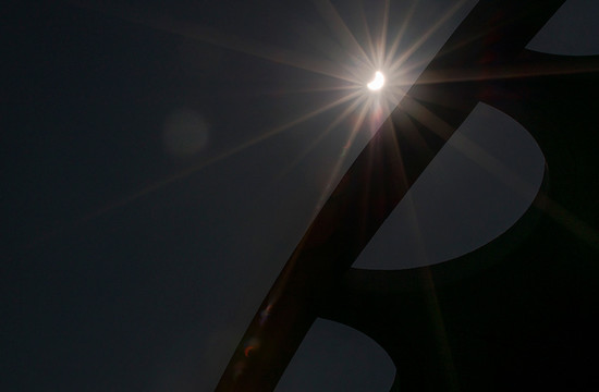 photo of the crescent-shaped sun near the roof line of Beckman Auditorium