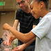 Caltech graduate student Michael Mazza helps a fourth-grade student strain strawberry pulp to extract its DNA.
