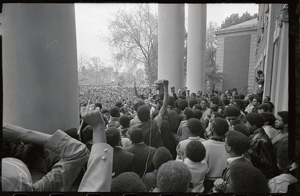"Olympic bronze medalist John Carlos (center, checkered hat), who was banished from the U.S. team and Olympic Village after employing ""black power"" gestures during the playing of the U.S. National Anthem, addresses a large student rally on the campus. / Credit: Bettmann"