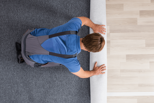 man on his knees rolling up laminate floor