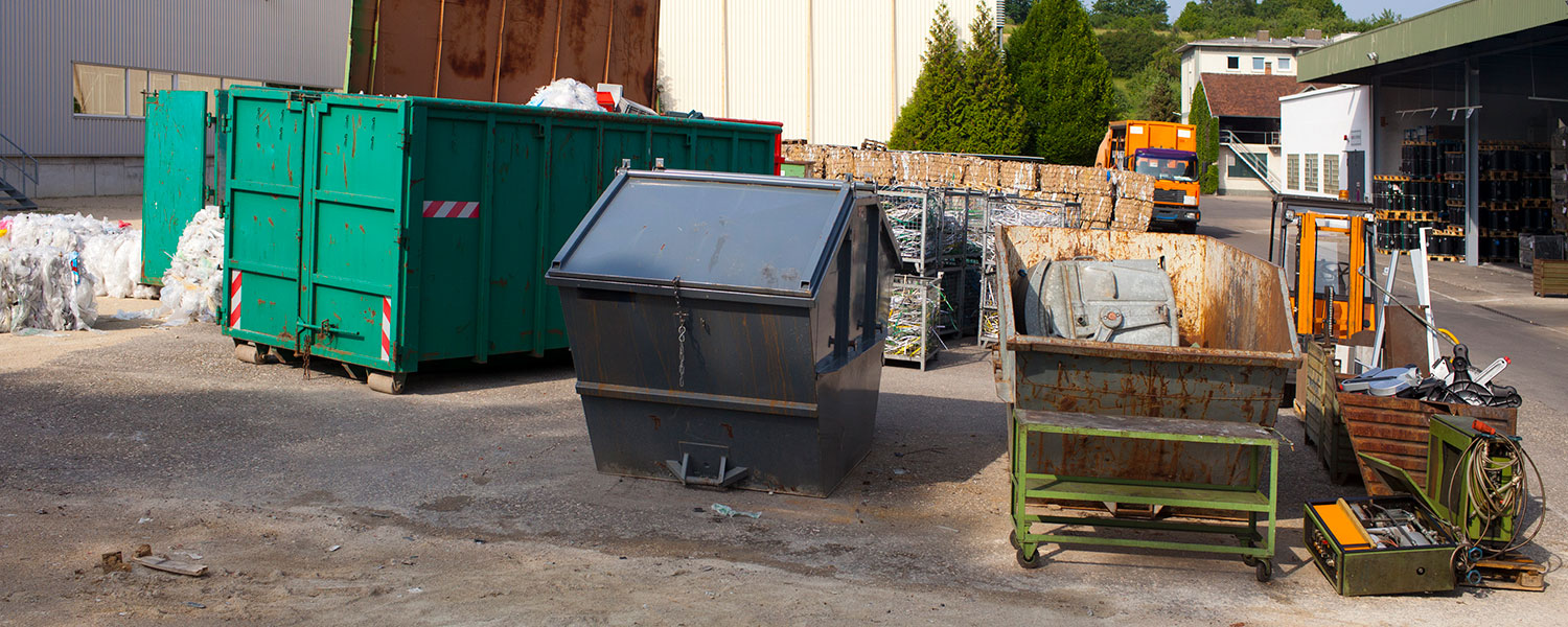 Multiple dumpsters on a job site including a construction dumpster and a small front load commercial dumpster.