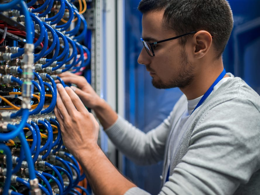 Man with glasses working with blue data cables and wiring
