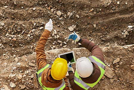 bird's eye view of two men working on a mining field pointing at the dirt and holding a tablet